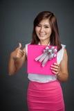 Härlig asiatisk flickashow en gåvaask och tummar upp Royaltyfri Fotografi