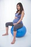 Härlig asiatisk gravid kvinna som gör övning med en schweizisk boll, royaltyfri fotografi