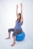 Härlig asiatisk gravid kvinna som gör övning med en schweizisk boll, fotografering för bildbyråer