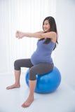 Härlig asiatisk gravid kvinna som gör övning med en schweizisk boll, arkivbild
