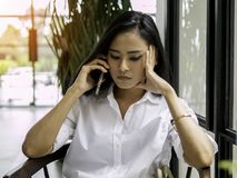 Härlig asiatisk hållande smartphone för affärskvinna i hand och allvarligt koncentrat som lyssnar en appell med bekymmer royaltyfri fotografi