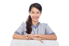 Härlig asiatisk hembiträde i likformig med det vita brädet Royaltyfria Bilder