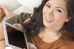 Härlig asiatisk kinesisk kvinna på minnestavladatoren Arkivbild