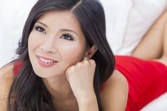 Härlig asiatisk kinesisk kvinnaflicka i röd klänning Fotografering för Bildbyråer