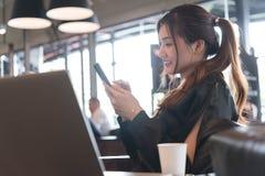 Härlig asiatisk kvinna i den svarta klänningen som arbetar med bärbara datorn och sma Arkivbild