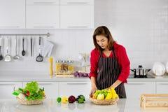 Härlig asiatisk kvinna i röd standking för skjorta och för svartförkläde arkivfoto