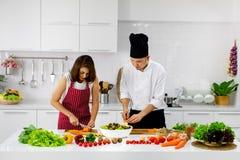 Härlig asiatisk kvinna i rött förkläde som lär hur man lagar mat och blandar arkivbild