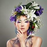 Härlig asiatisk kvinna med blomman på hennes huvud royaltyfri bild