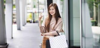 Härlig asiatisk kvinna med shoppingpåsar och ett kort fotografering för bildbyråer