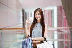 Härlig asiatisk kvinna med shoppingpåsar och ett kort royaltyfria foton