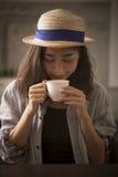 Härlig asiatisk kvinna och varm lycka för kaffekopp som ler framsidan arkivfoto