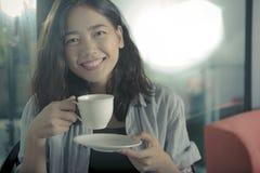 Härlig asiatisk kvinna och varm lycka för kaffekopp som ler framsidan arkivbild