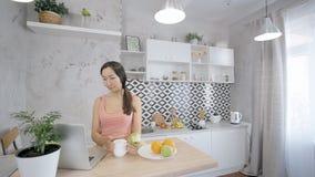 Härlig asiatisk kvinna som äter äpplet, medan att kontrollera knyter kontakt på hennes bärbar dator i köket arkivfilmer