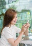 Härlig asiatisk kvinna som använder en smartphone Arkivbild