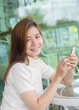 Härlig asiatisk kvinna som använder en smartphone Arkivfoton