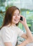 Härlig asiatisk kvinna som använder en smartphone Royaltyfria Bilder