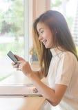 Härlig asiatisk kvinna som använder en smartphone Fotografering för Bildbyråer