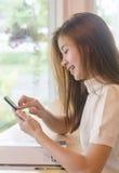 Härlig asiatisk kvinna som använder en smartphone Arkivfoto