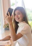 Härlig asiatisk kvinna som använder en smartphone Arkivbilder