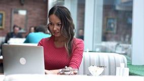 Härlig asiatisk kvinna som drömmer om något, medan sitta med den bärbara netto-boken i modern kaféstång Arkivfoton