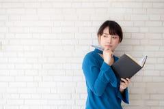 Härlig asiatisk kvinna som ler anseendet som tänker och skriver anteckningsboken på vit bakgrund för konkret cement royaltyfri foto