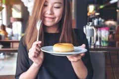 Härlig asiatisk kvinna som rymmer ett stycke av munken och gaffeln med mening lyckligt i kafé arkivbilder