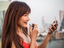 Härlig asiatisk kvinna som sätter makeupläppstift, lyckligt kvinnabegrepp som är filmiskt royaltyfri fotografi