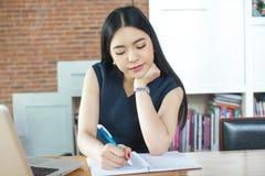 Härlig asiatisk kvinna som skriver en anteckningsbok på tabellen med bärbara datorn som royaltyfri fotografi