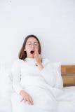 Härlig asiatisk kvinna som vaknar upp, och gäspning i säng i sovrummet Royaltyfri Fotografi