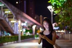 Härlig asiatisk kvinna utomhus på natten genom att använda mobiltelefonen arkivbild