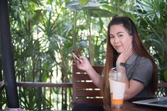 Härlig asiatisk kvinnahållsmartphone och se kameran, varv Arkivfoto