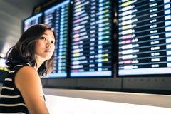 Härlig asiatisk kvinnahandelsresande på informationsskärmen om flyg i ett flygplats-, lopp- eller tidbegrepp arkivbilder