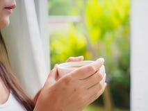 Härlig asiatisk kvinnlig som dricker en kopp kaffe på trädgården arkivbilder