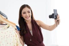 Härlig asiatisk le stilfull vlogger för flickamode som väljer dräkt i klädlagret som rymmer med selfievideoen själv, granskning royaltyfria foton