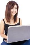 Härlig asiatisk maskinskrivning för ung kvinna på bärbara datorn Fotografering för Bildbyråer