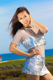 Härlig asiatisk modell i en silverklänning Royaltyfri Foto