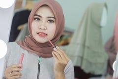 Härlig asiatisk muslimkvinna med hijab som applicerar läppstift royaltyfria bilder
