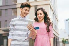 Härlig asiatisk parshopping med en kreditkort i staden arkivfoton