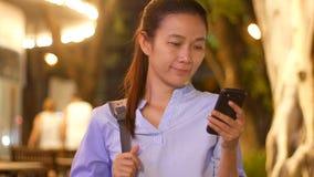 Härlig asiatisk ung affärskvinna som använder applikation på smsande pratstund för smart telefon med vännen på utomhus- med att l
