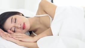 Härlig asiatisk ung kvinna som sover att ligga i säng med huvudet på bekväm och lycklig rörande panorera kamera för kudde lager videofilmer