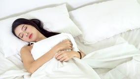 Härlig asiatisk ung kvinna som sover att ligga i säng med huvudet på bekväm och lycklig rörande panorera kamera för kudde stock video
