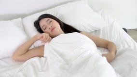 Härlig asiatisk ung kvinna som sover att ligga i säng med huvudet på bekväm och lycklig rörande panorera kamera för kudde flicka  stock video