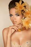 Härlig attraktiv flicka med guld- blommor Skönhetmodell Woma Arkivfoto