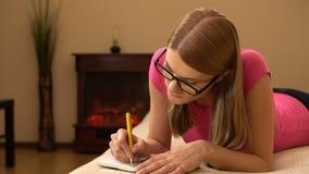 Härlig attraktiv handstil för ung kvinna i anteckningsbok Framställning av en lista och att tänka och le arkivfilmer