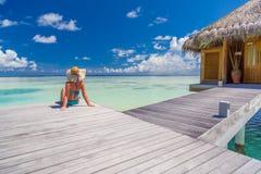 Härlig attraktiv kvinna i bikinin och hatten som ligger på strandträbryggan och den lyxiga vattenvillan Havssikt, lyxig livsstil arkivbilder
