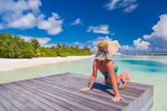 Härlig attraktiv kvinna i bikinin och hatten som ligger på strandträbryggan och den lyxiga vattenvillan Havssikt, lyxig livsstil royaltyfri fotografi