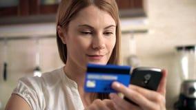 Härlig attraktiv kvinna i den vita t-skjortan som direktanslutet köper med kreditkorten på smartphonen Kök lager videofilmer