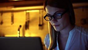 Härlig attraktiv kvinna i exponeringsglas som bläddrar internet på bärbara datorn Aftonkök lager videofilmer