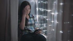 Härlig attraktiv kvinna som använder minnestavlaPC och sitter på fönsterbrädan som dekoreras med girlander arkivfilmer