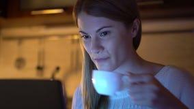 Härlig attraktiv kvinna som bläddrar internet och arbete på bärbara datorn Aftonkök dricka för kaffe arkivfilmer
